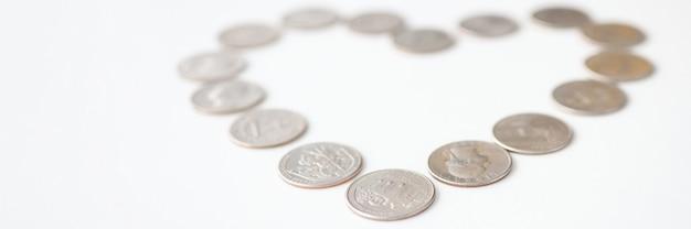 Zilveren munten liggen in de vorm van een hart op een witte achtergrond. liefde voor geld concept