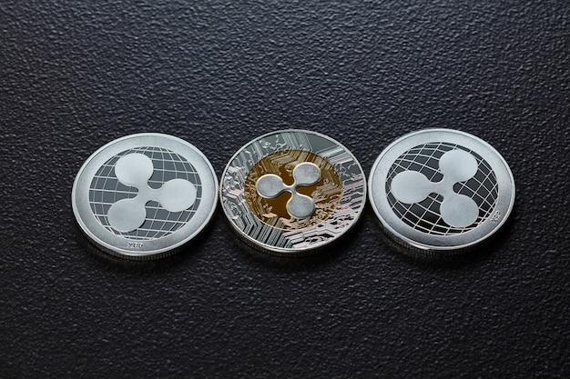 Zilveren munten zijn rimpel. de voor- en achterkant van de munten zijn weergegeven op een donkere achtergrond. virtueel geldconcept. bovenaanzicht
