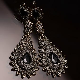 Zilveren oorbellen met zwarte steentjes op donker glas