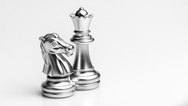 Zilveren paard en koningin schaken staan. - bedrijfswinnaar en vechtconcept.
