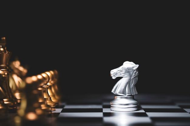 Zilveren paardschaak ontmoetingen met gouden schaakvijand op schaakbord en zwarte achtergrond.
