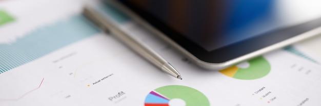 Zilveren pen en digitale tablet-pc liggen op kantoortafel op zakelijke grafiek