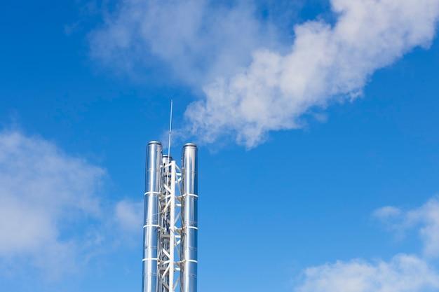 Zilveren pijp met stromende rook tegen de blauwe lucht. hoge kwaliteit foto