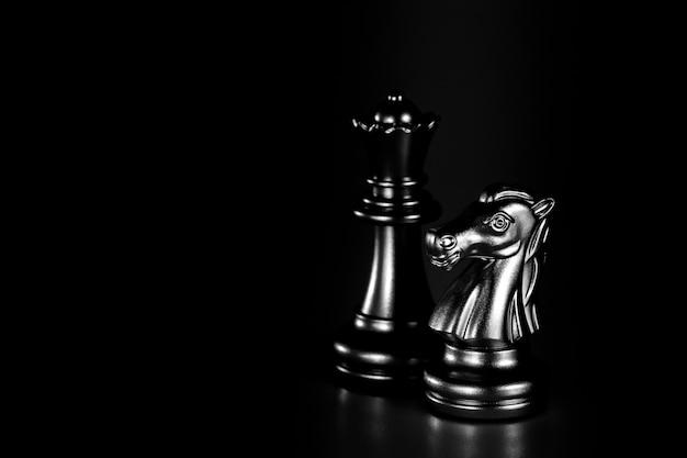 Zilveren ridder en koninginneschaak die zich in het donker bevinden. - bedrijfswinnaar en vechtconcept.
