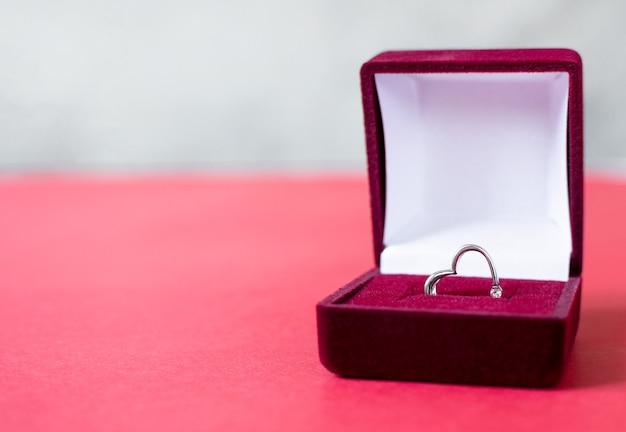 Zilveren ringhart in rode doos. valentijnsdag voorstel gebaar aanwezig.
