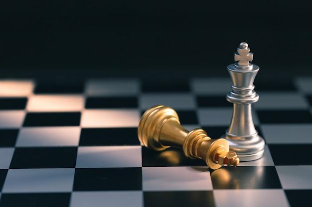 Zilveren schaakkoning staande en gouden schaakkoning vallen op schaakbord