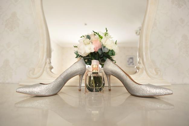 Zilveren schoenen van de bruid, parfum, boeket en trouwringen op de kaptafel bij de spiegel