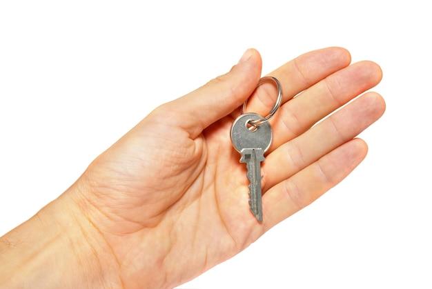 Zilveren sleutel in een hand die op wit wordt geïsoleerd.