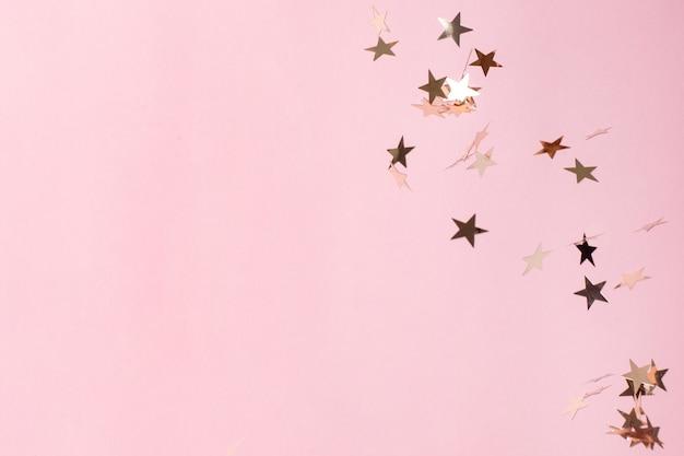 Zilveren ster confetti op pastel roze achtergrond.