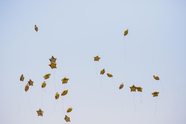 Zilveren sterballon op hemel met kleurenfilters.