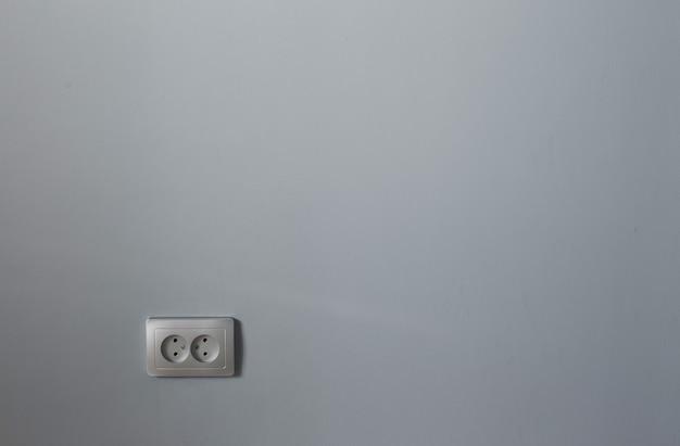 Zilveren stopcontact op grijze muur