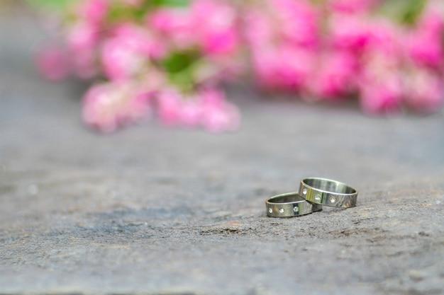 Zilveren trouwringen en roze bloemen