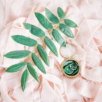 Zilveren trouwringen liggen op de roze doek onder groene bladeren