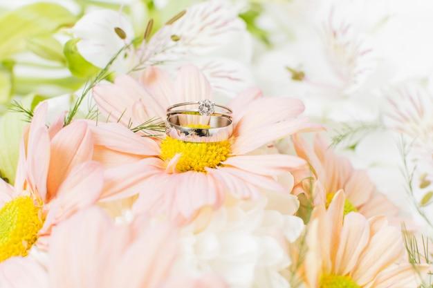 Zilveren trouwringen op roze gerberabloemboeket