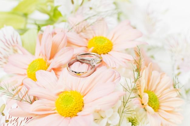Zilveren trouwringen op roze gerberabloemen