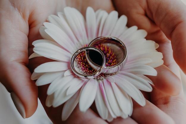 Zilveren trouwringen tegen bloem op de handen van de vrouw
