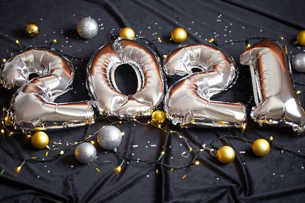 Zilverfolie ballonnen gemaakt nieuwjaarsnummer op zwarte achtergrond met garland en ballen.