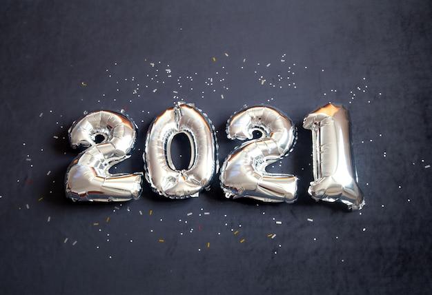 Zilverfolie ballonnen gemaakt nieuwjaarsnummer op zwarte achtergrond.