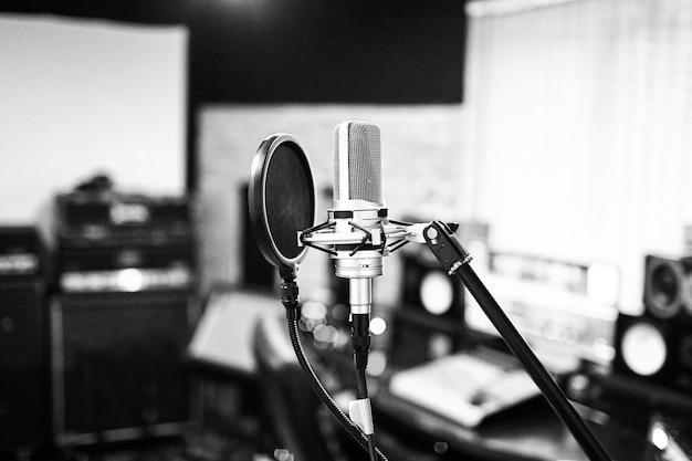 Zilverkleurige condensatormicrofoon met popfilter en trillingsdempende houder. muziek studio