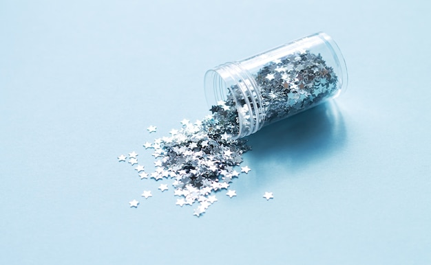 Zilverkleurige confetti die uit glazen fles valt, materiaal voor doe-het-zelf- of vakantiedecor