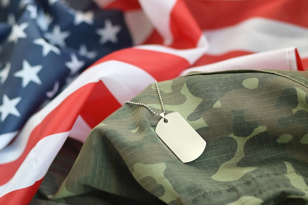 Zilverkleurige militaire kralen met dog tag op amerikaanse stoffen vlag en camouflage uniform