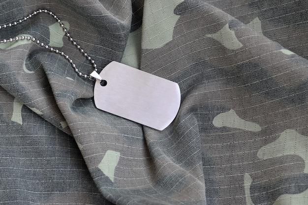 Zilverkleurige militaire kralen met dog tag op camouflage vermoeidheid uniform