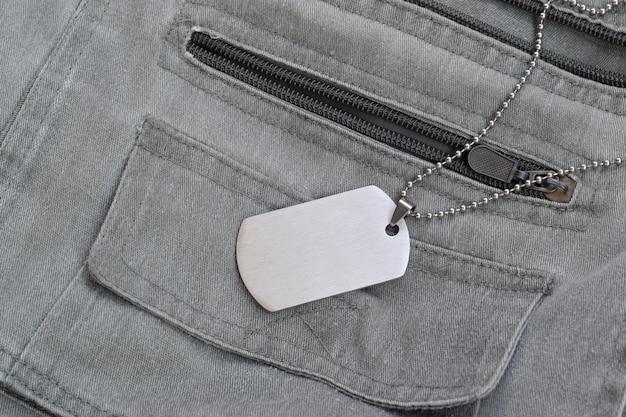 Zilverkleurige militaire kralen met dog tag op donkergrijs vest met zakken