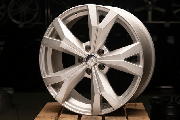 Zilverkleurige nieuwe gegoten aluminium wielen op een zwarte achtergrond close-up