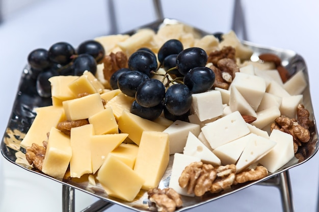 Zilverplaatje met kaasdruiven en noten. lekker voorgerecht. plaat van kaas op witte plaat in een restaurant