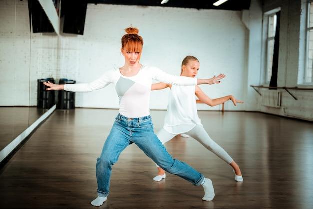 Zin in dansen. roodharige balletleraar en haar student die witte kleding draagt die in de dansschool oefent