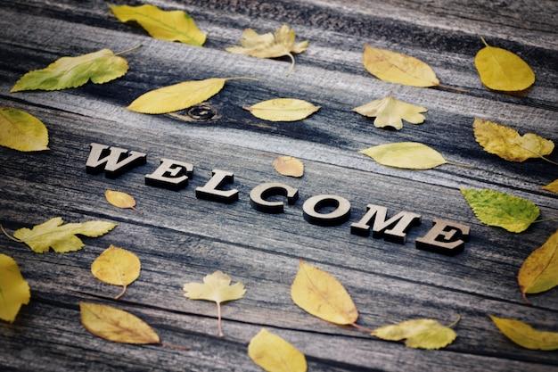 Zin welkom op een houten achtergrond, frame van gele bladeren
