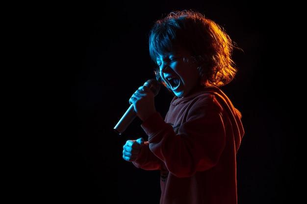 Zingen als een beroemdheid, rockster. het portret van de kaukasische jongen op donkere studioachtergrond in neonlicht. prachtig krullend model. concept van menselijke emoties, gezichtsuitdrukking, verkoop, advertentie, muziek, hobby, droom.