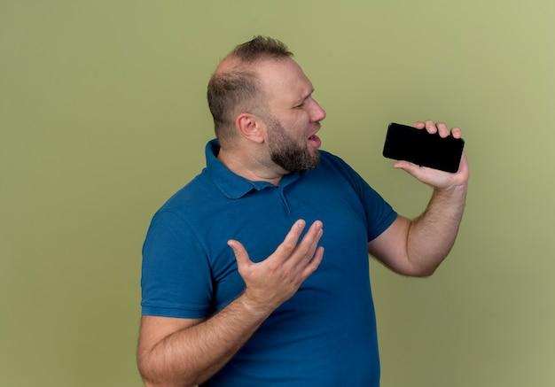 Zingen met gesloten ogen volwassen slavische man hand in de lucht houden met behulp van mobiele telefoon als microfoon