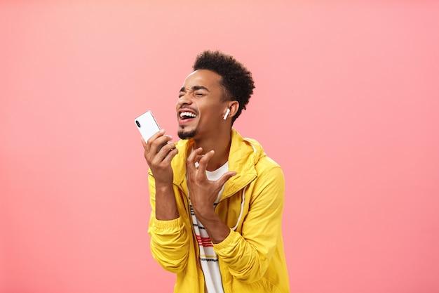 Zingen uit de grond van het hart langs favoriete muziek luisteren lied in draadloze oordopjes met gesloten ogen en vrolijke glimlach gebaren hartstochtelijk microfoon maken van smartphone over roze achtergrond.