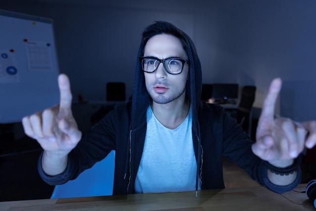 Zintuiglijk scherm. aardige, aangename, bebaarde man die aan de tafel zit en naar zijn vingers kijkt terwijl hij op het sensorische scherm werkt