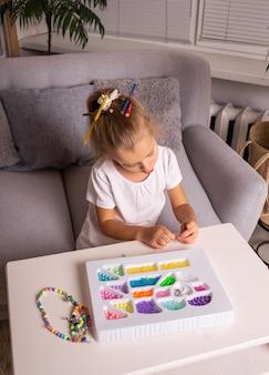 Zintuiglijke spelletjes met kleurrijke kralen met een kind thuis