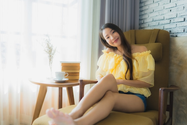 Zit de portret jonge aziatische vrouw op bankstoel en las boek met koffiekop