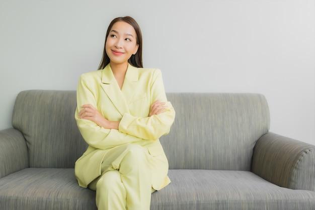 Zit de portret mooie jonge aziatische vrouw met glimlach op bank in woonkamerbinnenland