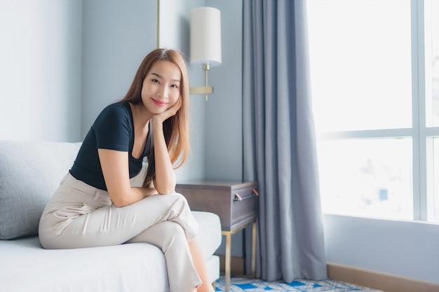 Zit de portret mooie jonge aziatische vrouw op bank op woonkamergebied ontspant