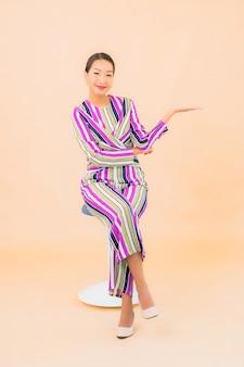 Zit de portret mooie jonge aziatische vrouw op stoel en glimlacht met actie op kleur