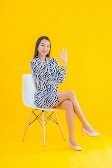 Zit de portret mooie jonge aziatische vrouw op stoel met actie betreffende geel