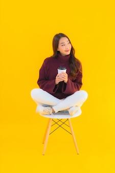 Zit de portret mooie jonge aziatische vrouw op stoel met gele geïsoleerde achtergrond