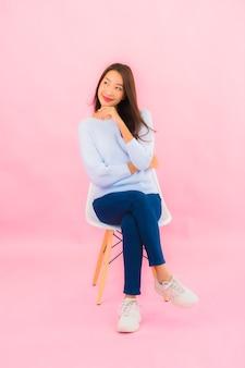 Zit de portret mooie jonge aziatische vrouw op stoel met roze kleurenmuur