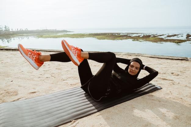Zit de sport moslimvrouw met hijab omhoog