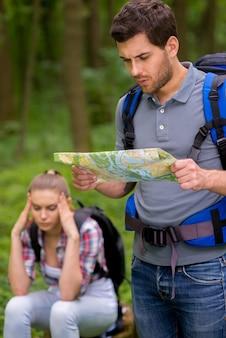 Zit ergens in het bos. nadenkende jonge man met rugzak die kaart in het bos onderzoekt terwijl een vrouw op de achtergrond zit en het hoofd in de hand houdt