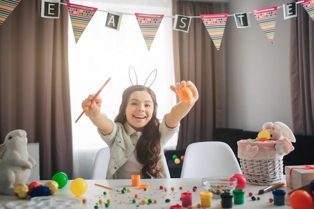 Zit het hapy positieve meisje bij lijst in ruimte en schilderend eieren