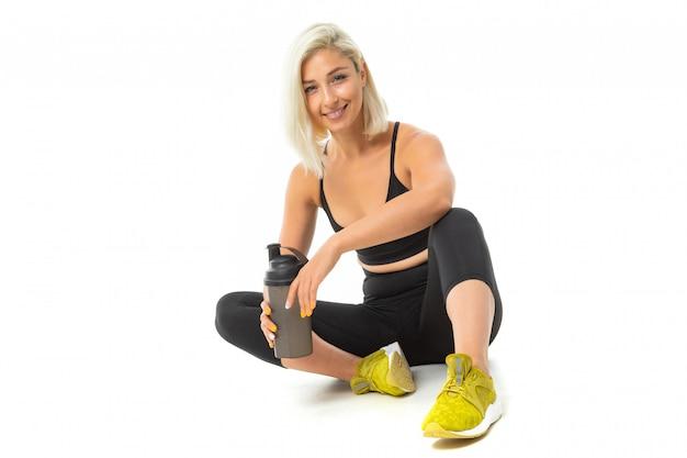 Zit het sport kaukasische meisje op een vloer in sportslijtage en houdt een fles met water in haar handen