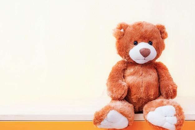 Zit het teddybeer gevulde stuk speelgoed op plank op gele achtergrond.
