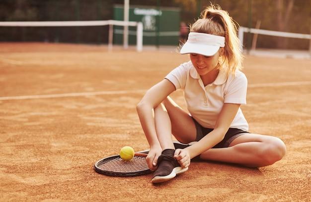 Zit op de grond. jonge tennisspeelster in sportieve kleding is buiten op het veld.