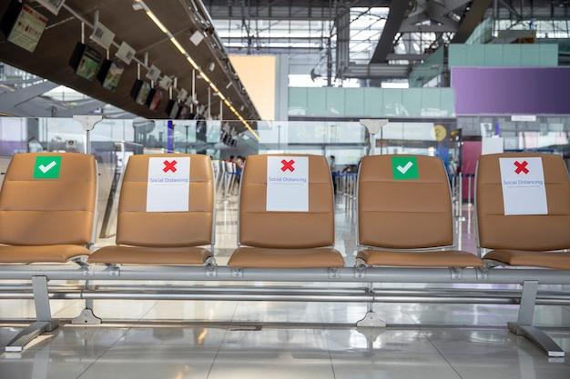 Zitplaats op openbaar in het openbaar met borden sociale afstand nemen bescherming voor één zitplaats afstand houden tot beschermende verspreiding voor covid-19 of coronavirus, sociaal afstandsconcept